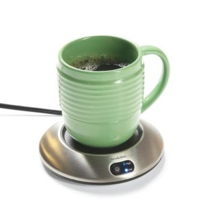 Green ceramic mug on cup warming pad